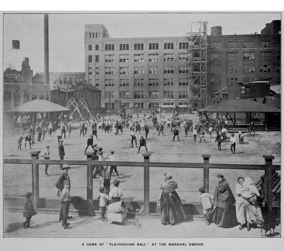Children play baseball inside a playground with large buildings in the background