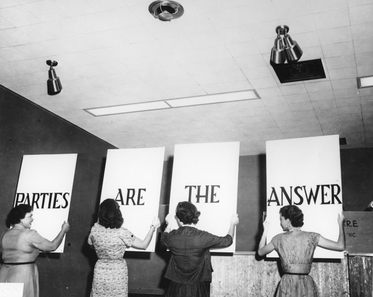"Photograph of a group of women hanging four signs that, together, say ""Parties are the answer."""