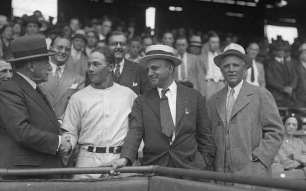 Joe Cambria stands in the foreground, smiling, flanked by onlookers in the stands and a baseball player