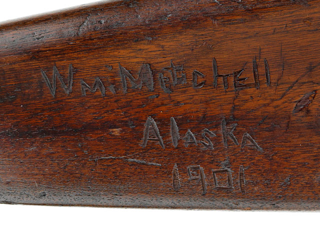 "Detail of rifle stock with the hand-carved inscription ""Wm. Mitchell / Alaska / 1901"""