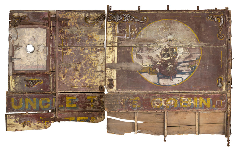 """Wagon panels after conservation. The panel;s decoations include oa large piece of art, depicting the scene of Eliza and her child fleeing across the Ohio River, pursued by leaping dogs. Also visible are the words, printed in large yellow and blue font, """"U"""