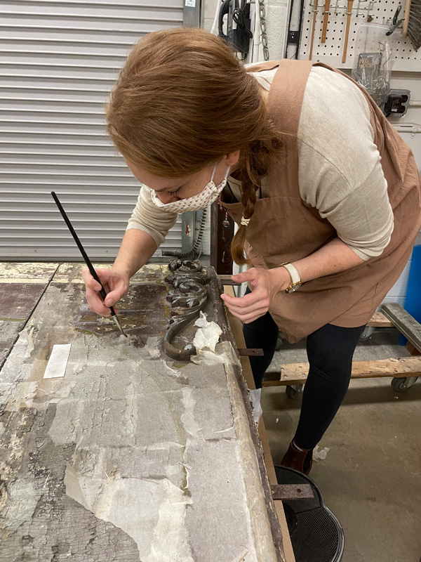 Conservator working behind the scenes at the museum, carefully removing tissue from the wagon panels