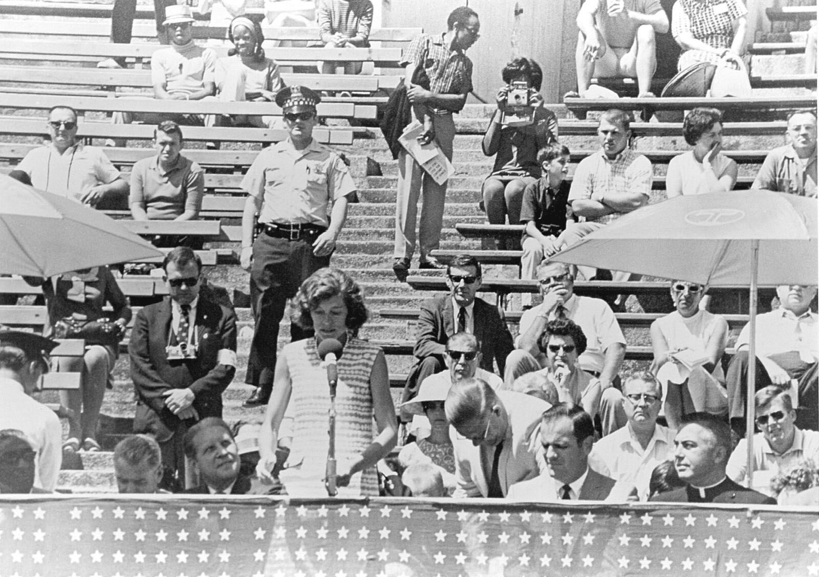 Black and white photo of people on bleachers watching a woman speak at a microphone.