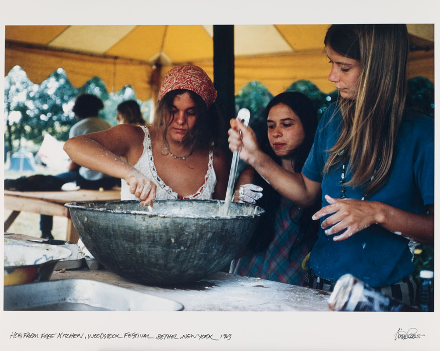 Women mix a white mixture in a large bowl, under a tent.
