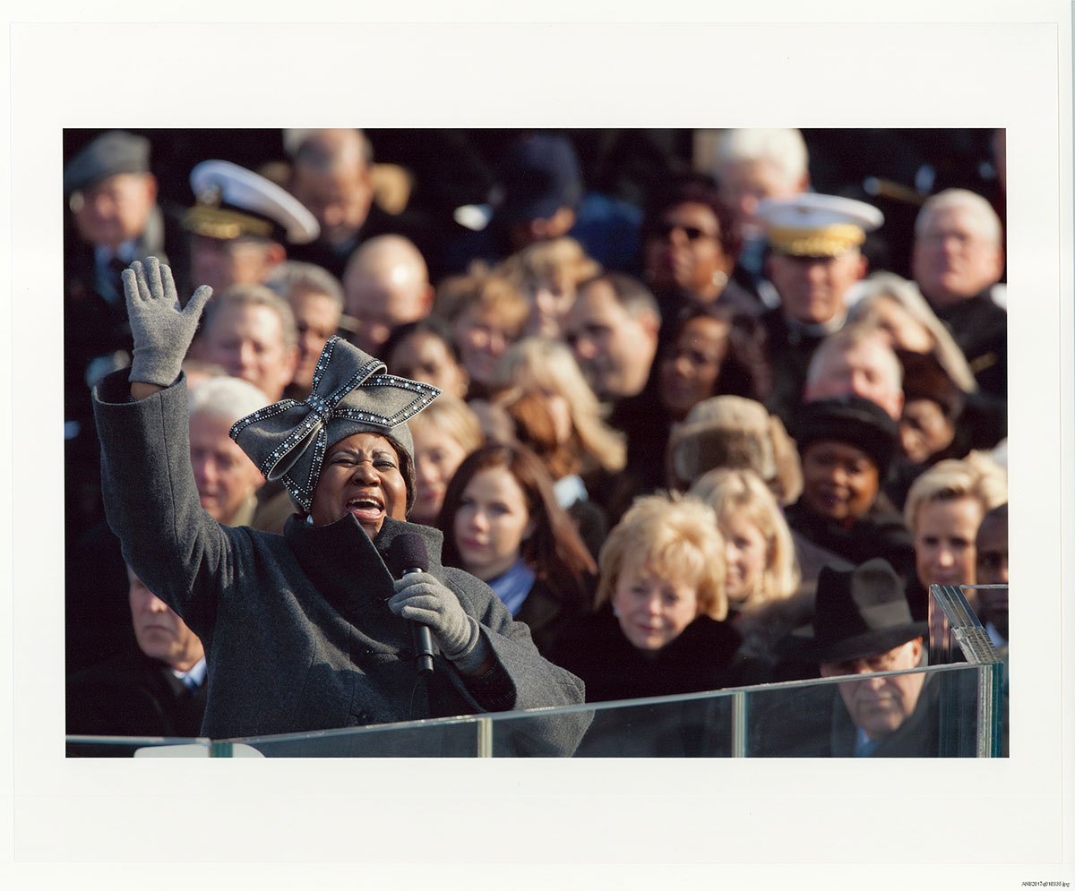 Photo of Aretha Franklin performing at Pres. Obama's inauguration, hand raised in the air and mouth open in song. Grey gloves, coat, and hat with large grey bow.