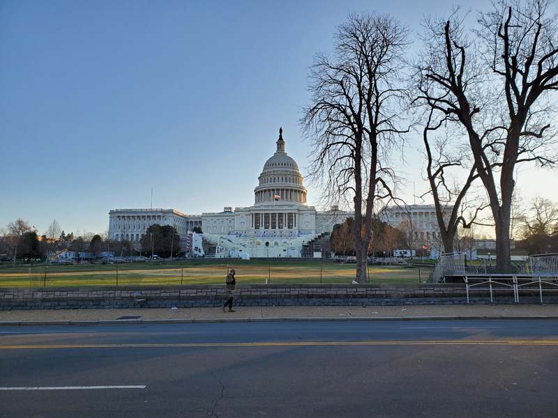 Photo of the Capitol Building from the National Mall, with a person in a military uniform walking in the foreground