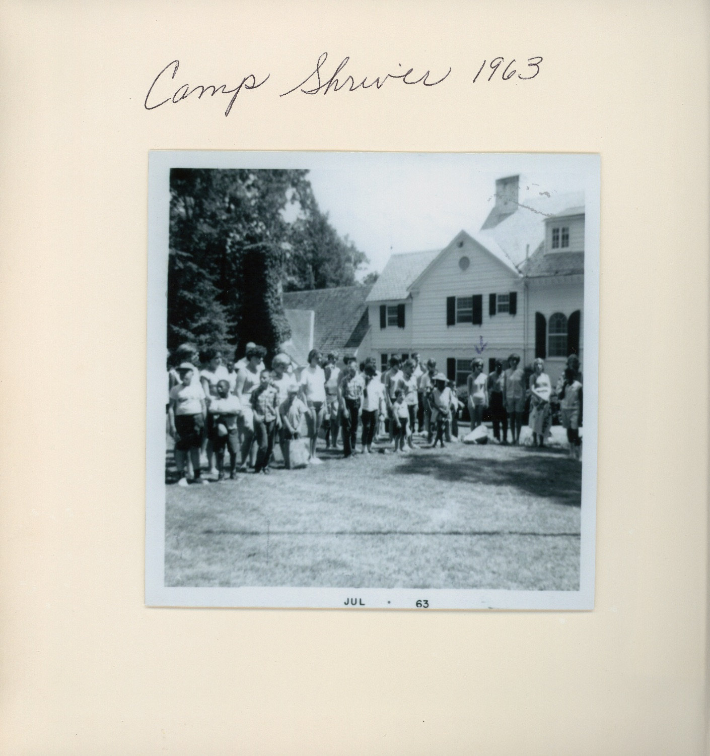 Black and white photo of group of young adults and adults in summer, sporty outfits posing in front of a house.