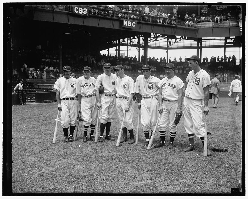 Black and white photo of seven baseball players in uniform, each holding a baseball bat. They're in a stadium that isn't completely full of fans, standing in the grass. Some smile. Two Red Sox uniforms, three Yankees. All wear ball caps.
