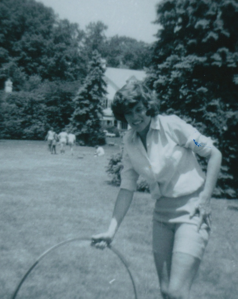 Photograph, in black and white, of a woman with short, curly hair on a lawn. She plays with or holds a hoola-hoop.