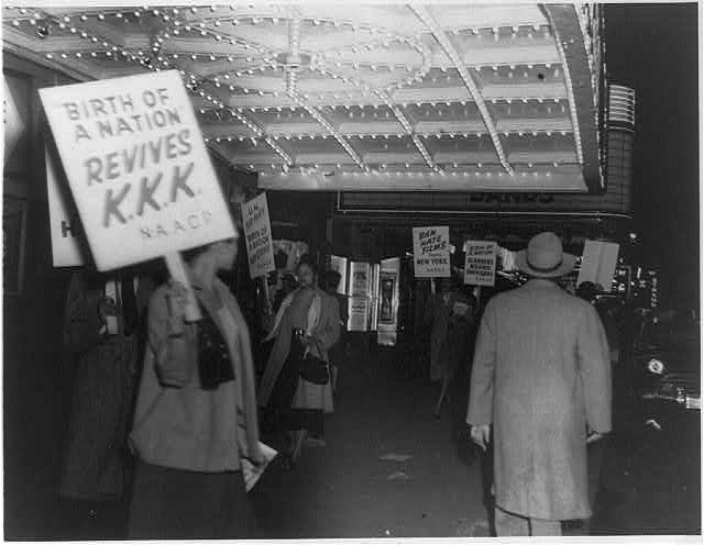 "Black and white photograph outside movie theater. Woman in front holds sign ""Birth of a Nation Revives KKK. NAACP."" Marquee of theater is visible. Other people also picket."