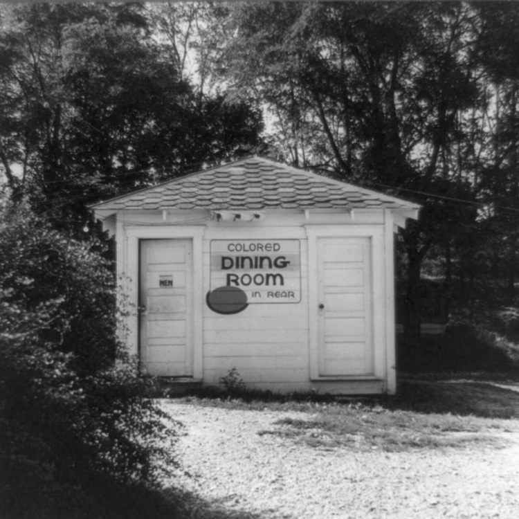 "Rest stop bathroom with sign ""Colored Dining Room in Rear"""