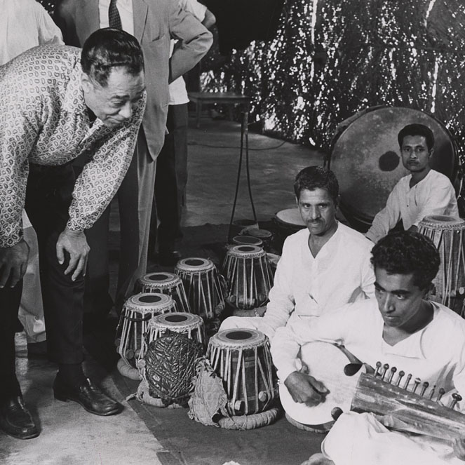 Duke Ellington watches Indian musicians play on traditional instruments