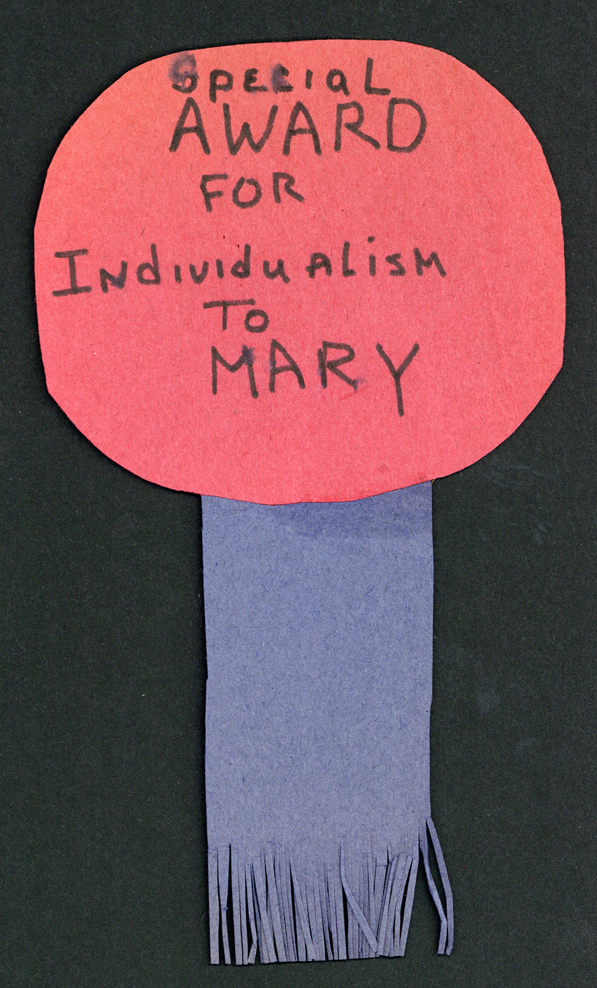 "Photo of a handmade award. A red piece of paper is cut into a circle with a blue ribbon. It says ""Special award for individualism to Mary"" in marker"