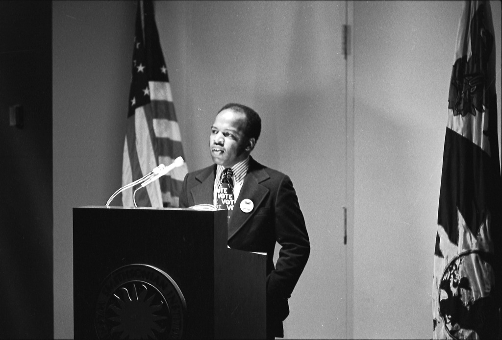 "John Lewis speaking at a podium wearing a ""Vote"" tie."