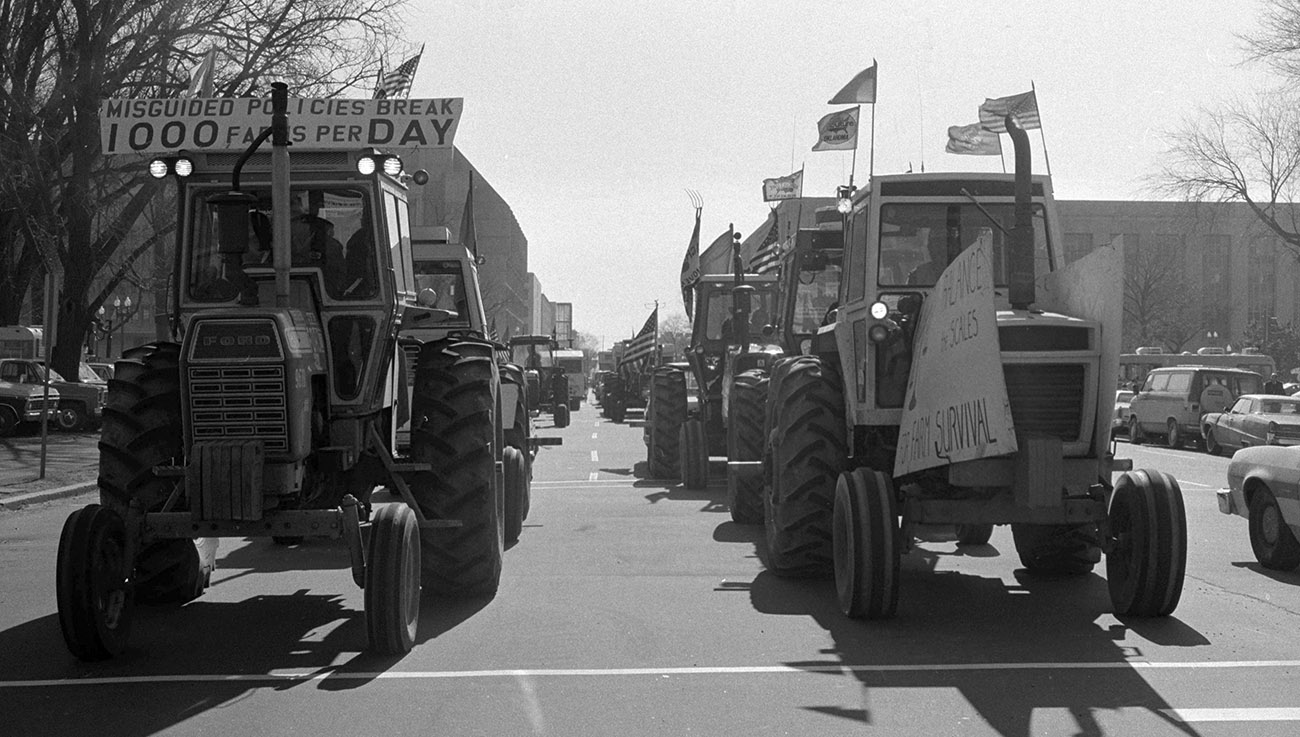 A black and white photograph of tractors as far as the eye can see on Constitution avenue.
