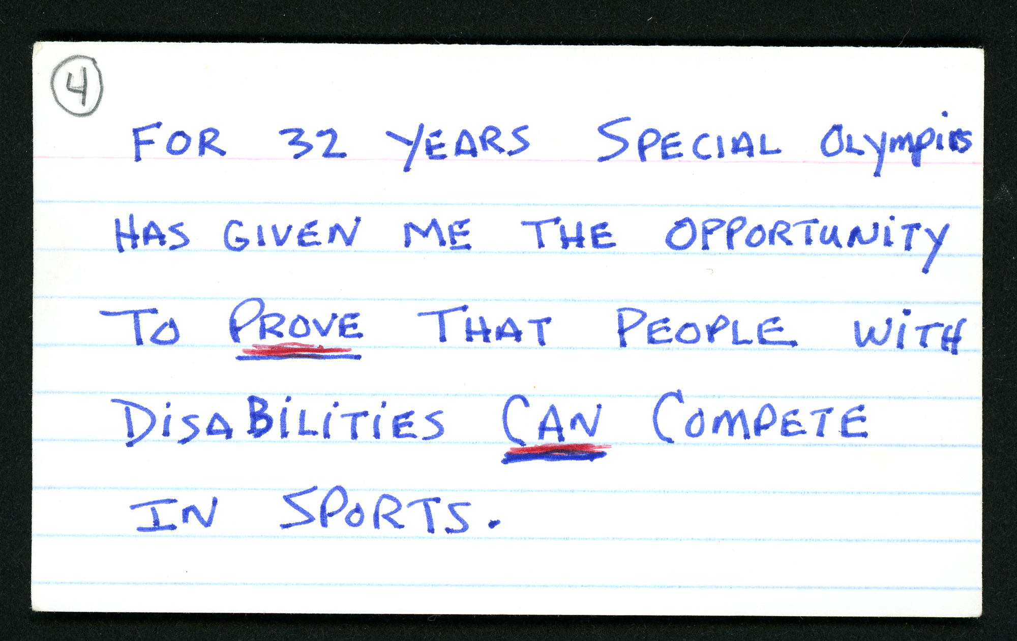 "White note-card with handwritten text: ""For 32 years Special Olympics has given me the opportunity to prove that people with disabilities can compete in sports."" in blue pen."