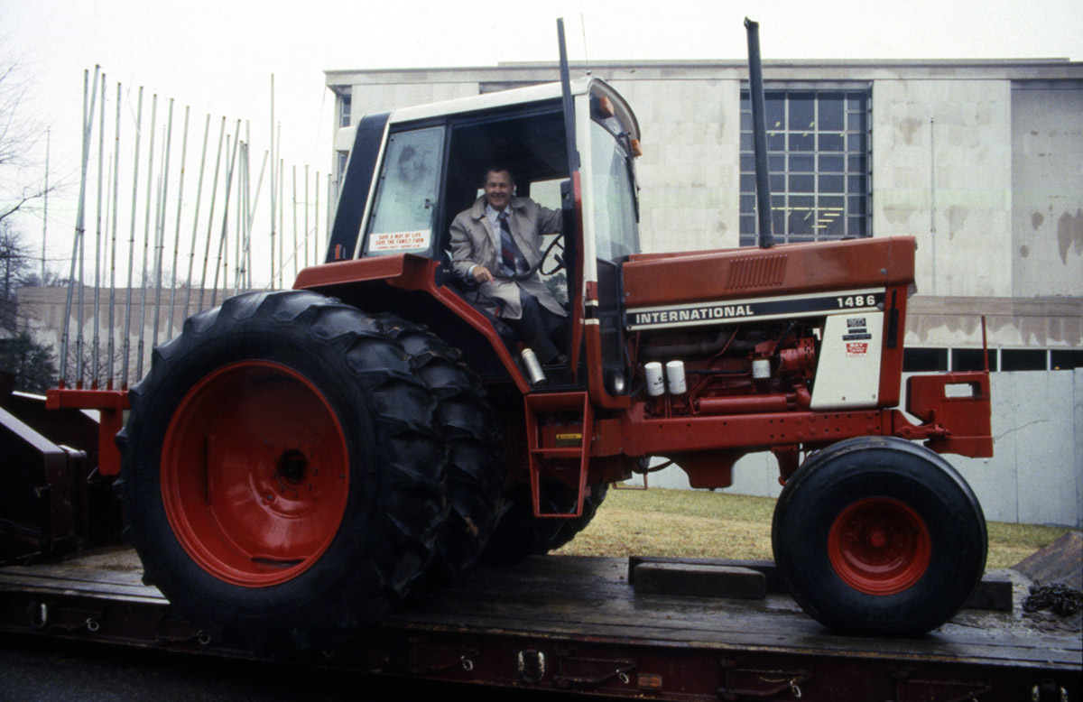 Gerald McCathern waving from atop his orange International Harvester tractor.