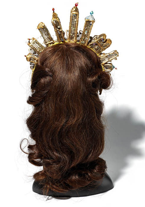 A brown wig with curls, photographed from the back of the head. It wears a gold crown that mirrors the New York skyline.
