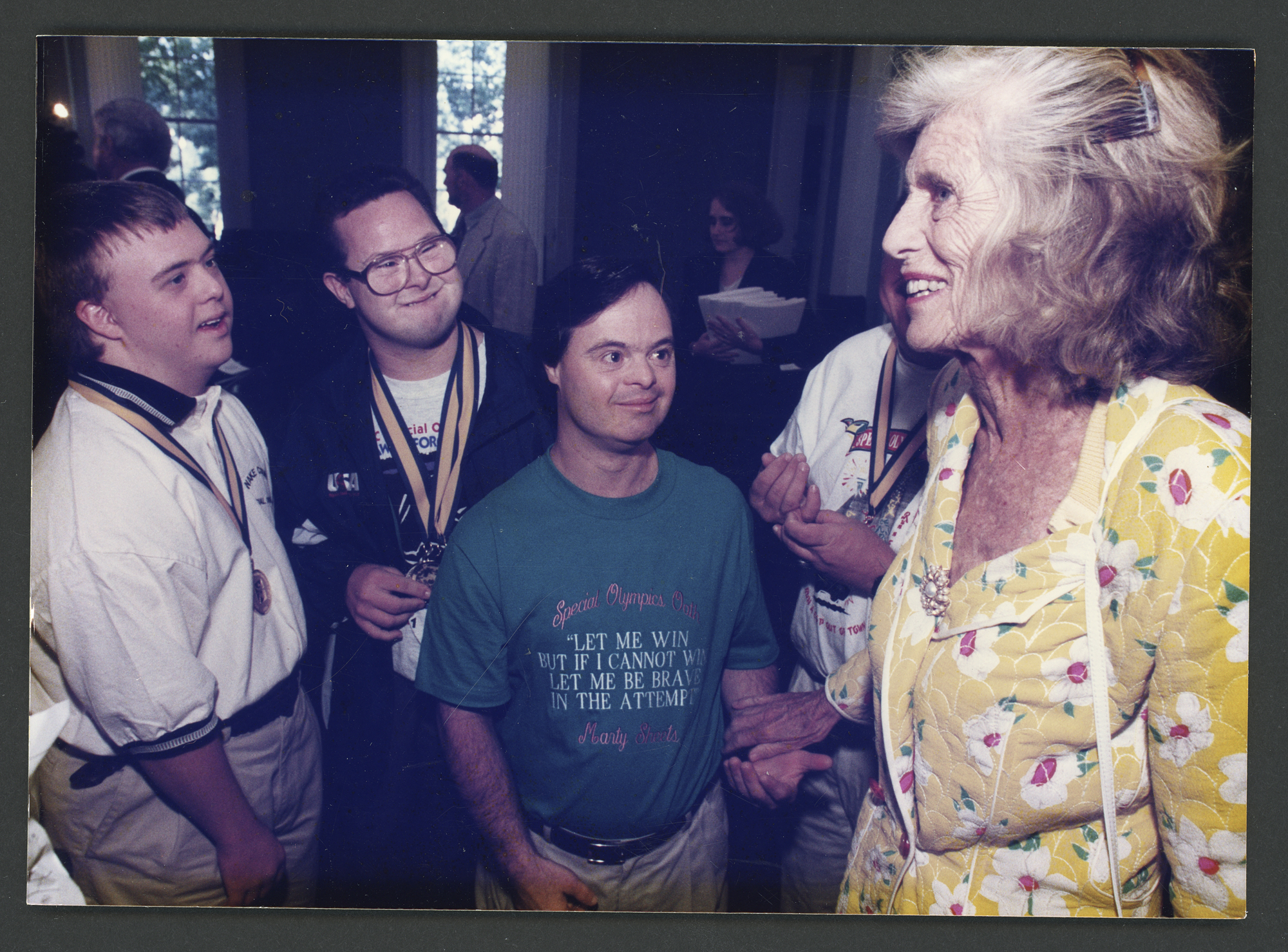 Color photo of Eunice Kennedy Shriver smiling at four Special Olympics participants. One young man wears a shirt with a Shriver quote on it.