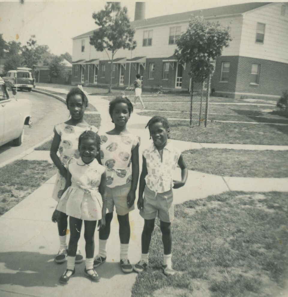 Black and white photo of four kids outside homes in a neighborhood. They all wear socks and tennis shoes as well as summery outfits, with one in a cute dress. They are African American and smiling.