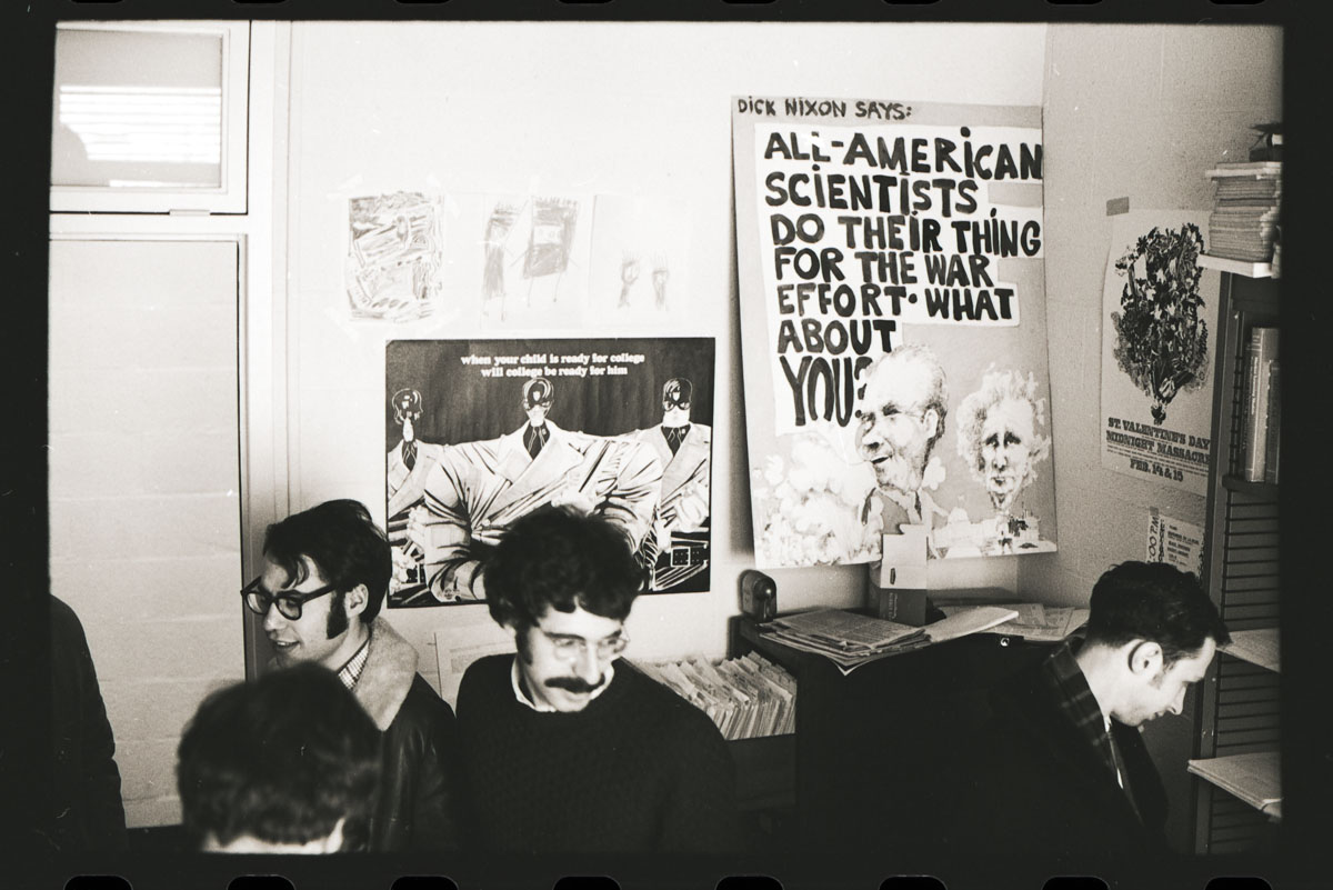 Students stand in front of posters.