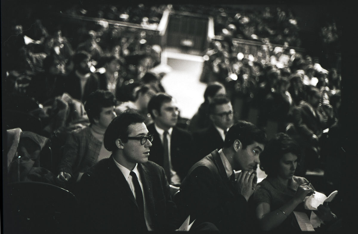 Men and one woman sit in an auditorium.