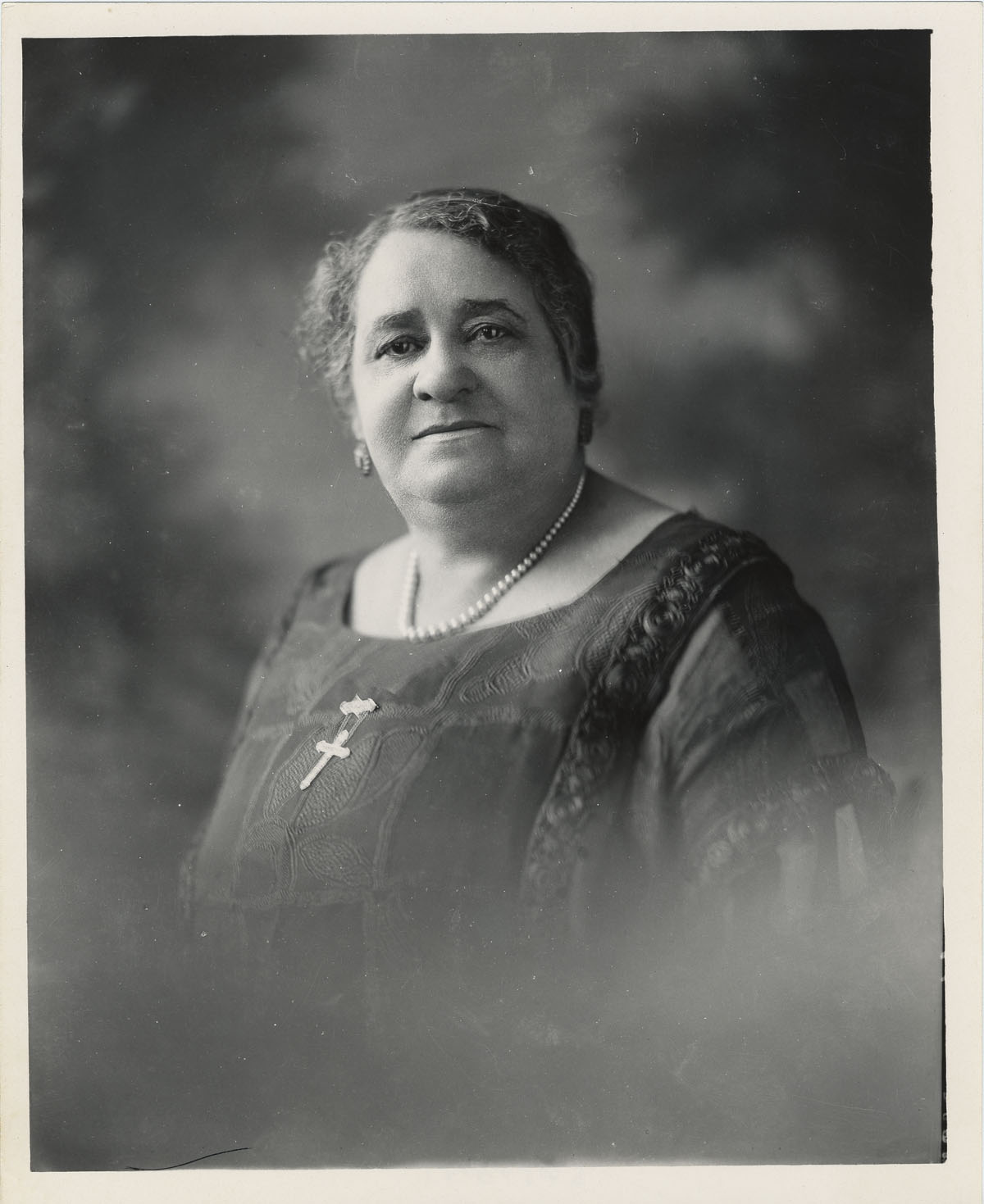 A portrait of a woman. She wears a cross on a necklace.