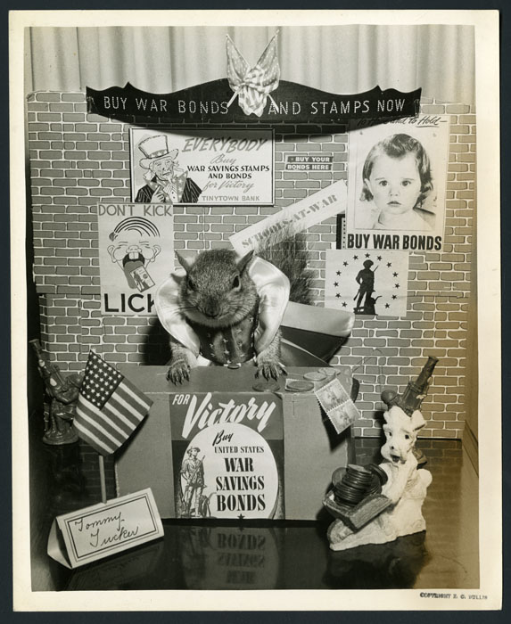 "Tommy Tucker leans on a small desk. The desk is decorated with ""buy war bonds"" posters."