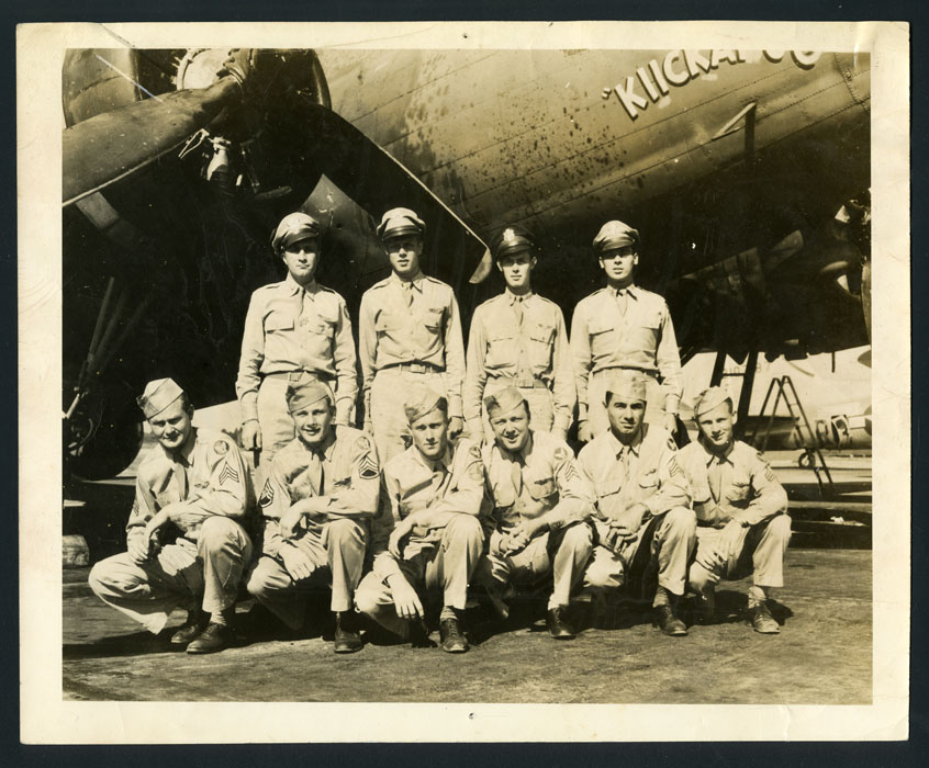 Men in uniform pose in front of an airplane.