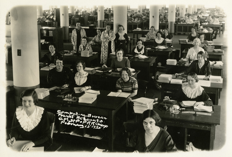 Dozens of women seated behind rows of desks in a large office space