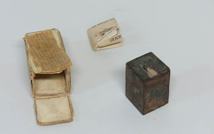 A box with a letter, and rectangular weight.