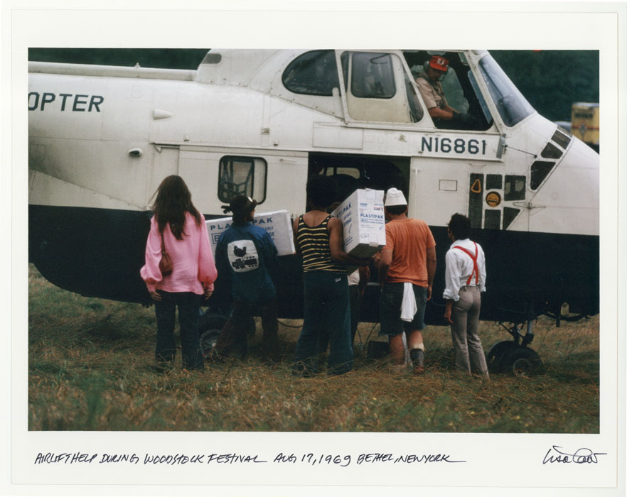 People load or unload boxes from a helicopter.