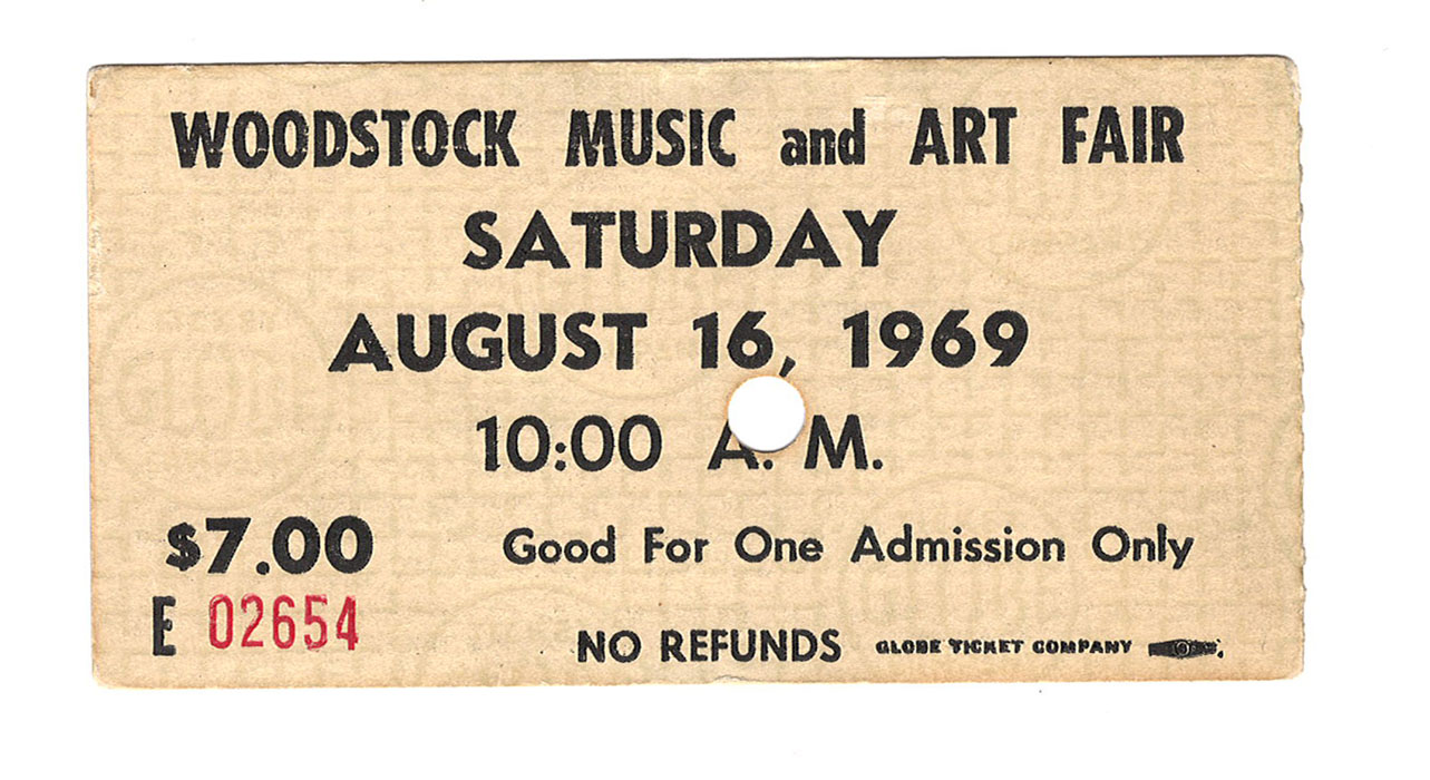 "A manila colored ticket with a circular hole punch in the middle. The text reads ""Woodstock Music and Art Fair, Saturday, August 16, 1969."""