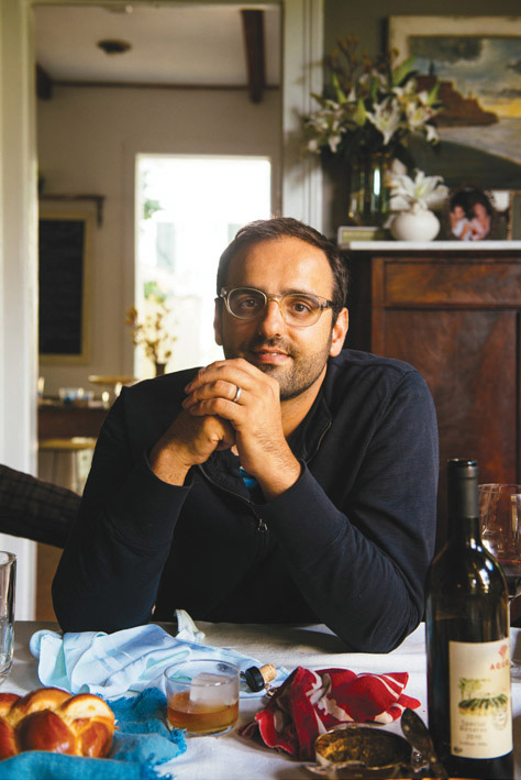 Chef Alon Shaya seated at a table