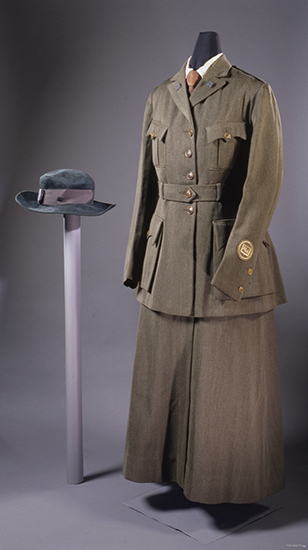 Dark brown uniform with collared jacket, two breast pockets, and floor-length skirt in same color. Navy blue hat.