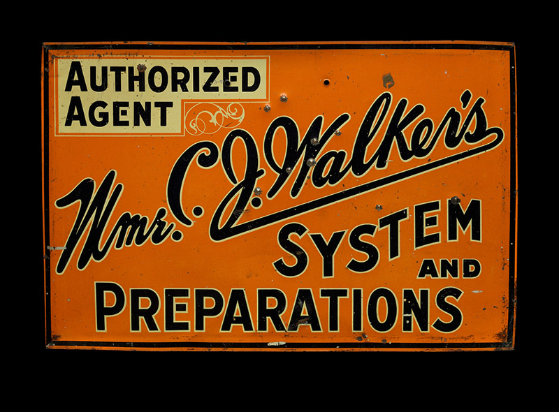 "An orange sign with black text reading ""Authorized Agent: Mme. C.J. Walker's System and Preparations."""