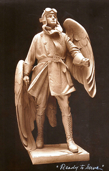 White sculpture of a man with flying goggles and flight helmet. He wears a billowing coat and boots. He has two wings in the style of an angel and looks to sky with an open, peaceful expression.