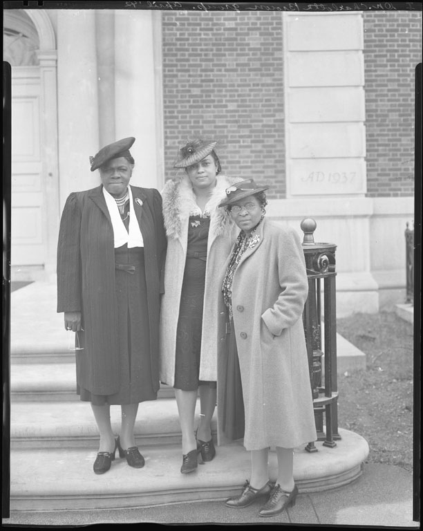 A black and white photograph of three African American women standing on the steps of a building. They all wear coats, hats, broaches, and stockings. The woman on the far left stares down the camera with determination.
