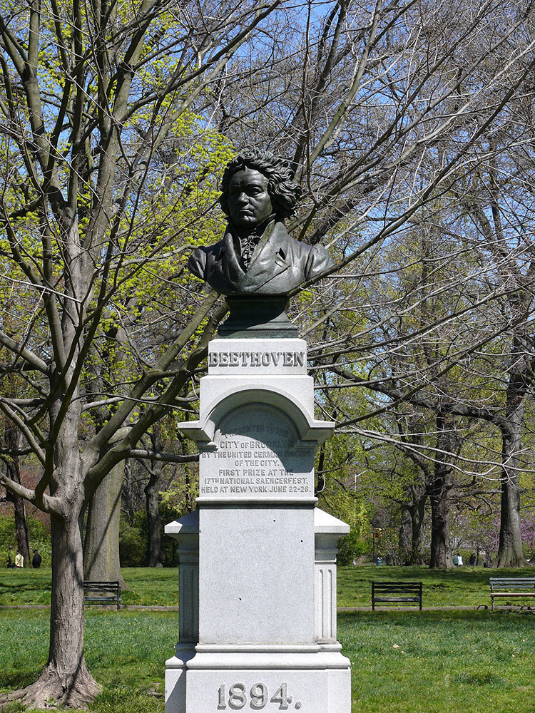 Photograph of bust on top of a stone pedestal in a park