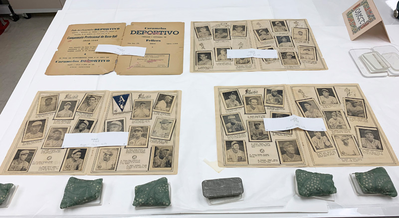 Four two-page spreads from Caramelo Deportivo baseball card album, separated and laid flat on a table in the museum's conservation lab