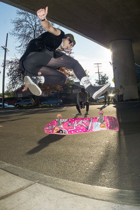 A skateboarder doing a trick with a pink skateboard.