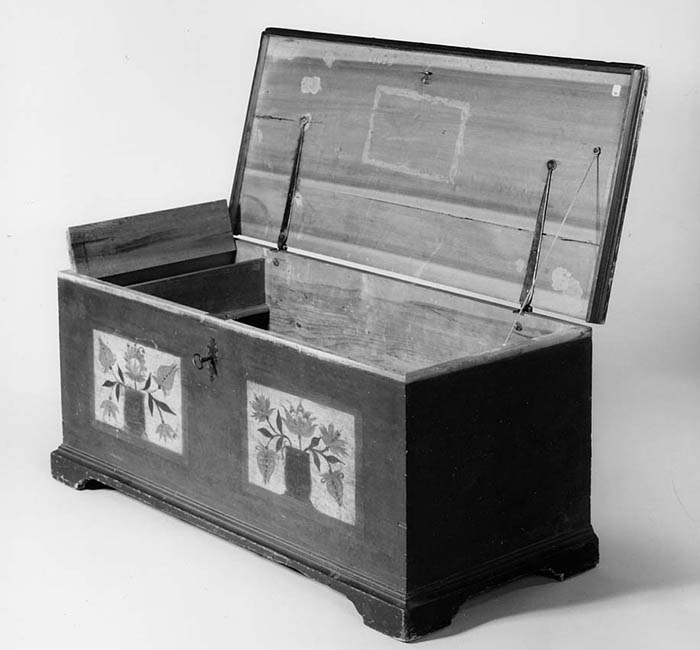 A black and white photograph of a chest with two flowered designs on the front.