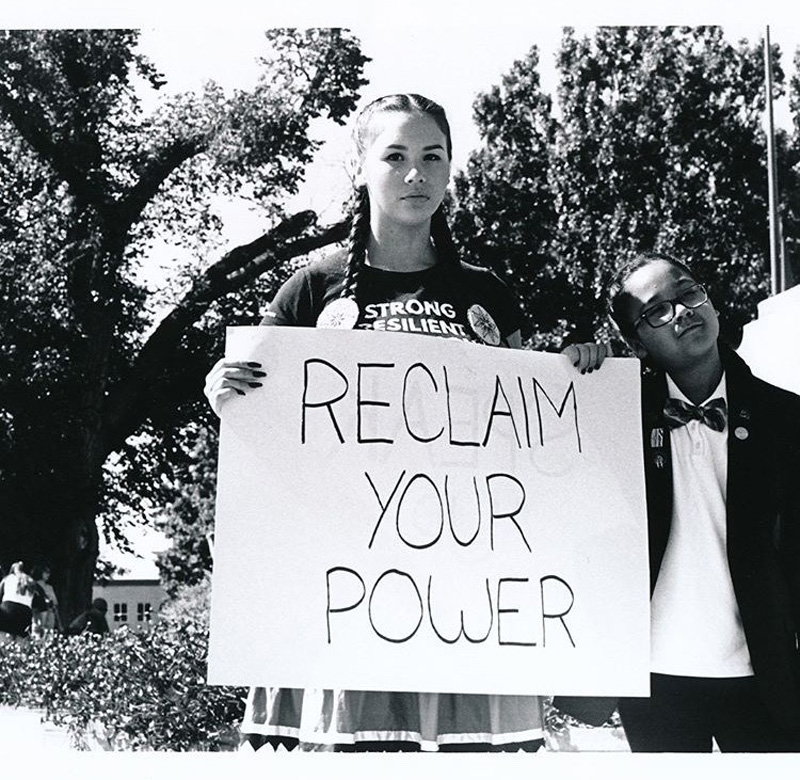 Isabella Aiukli Cornell holding sign, Reclaim Your Power