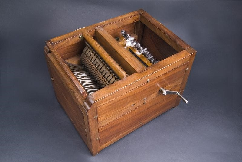 Wooden box with wisps of cotton in gears.
