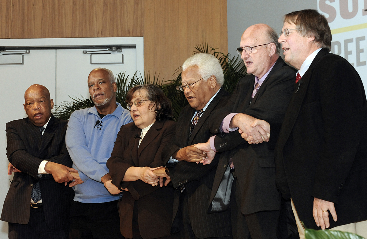 John Lewis crosses arms and sings We Shall Overcome with other Civil Rights leaders.