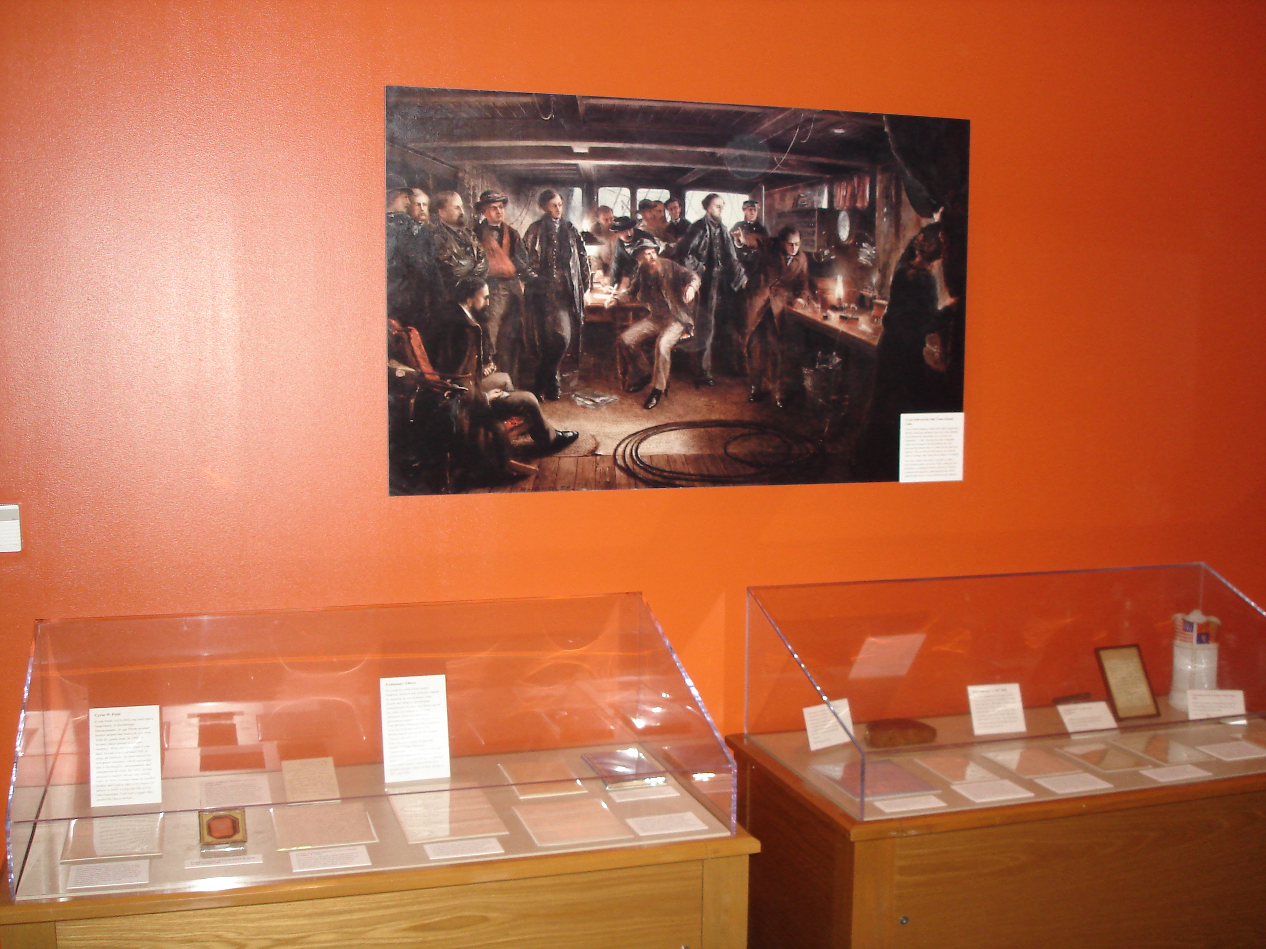 Two display cases sit next to an orange wall underneath a painting of a group of men from what appears to be the 1800s. In the display cases are papers and documents with note cards containing information about them.