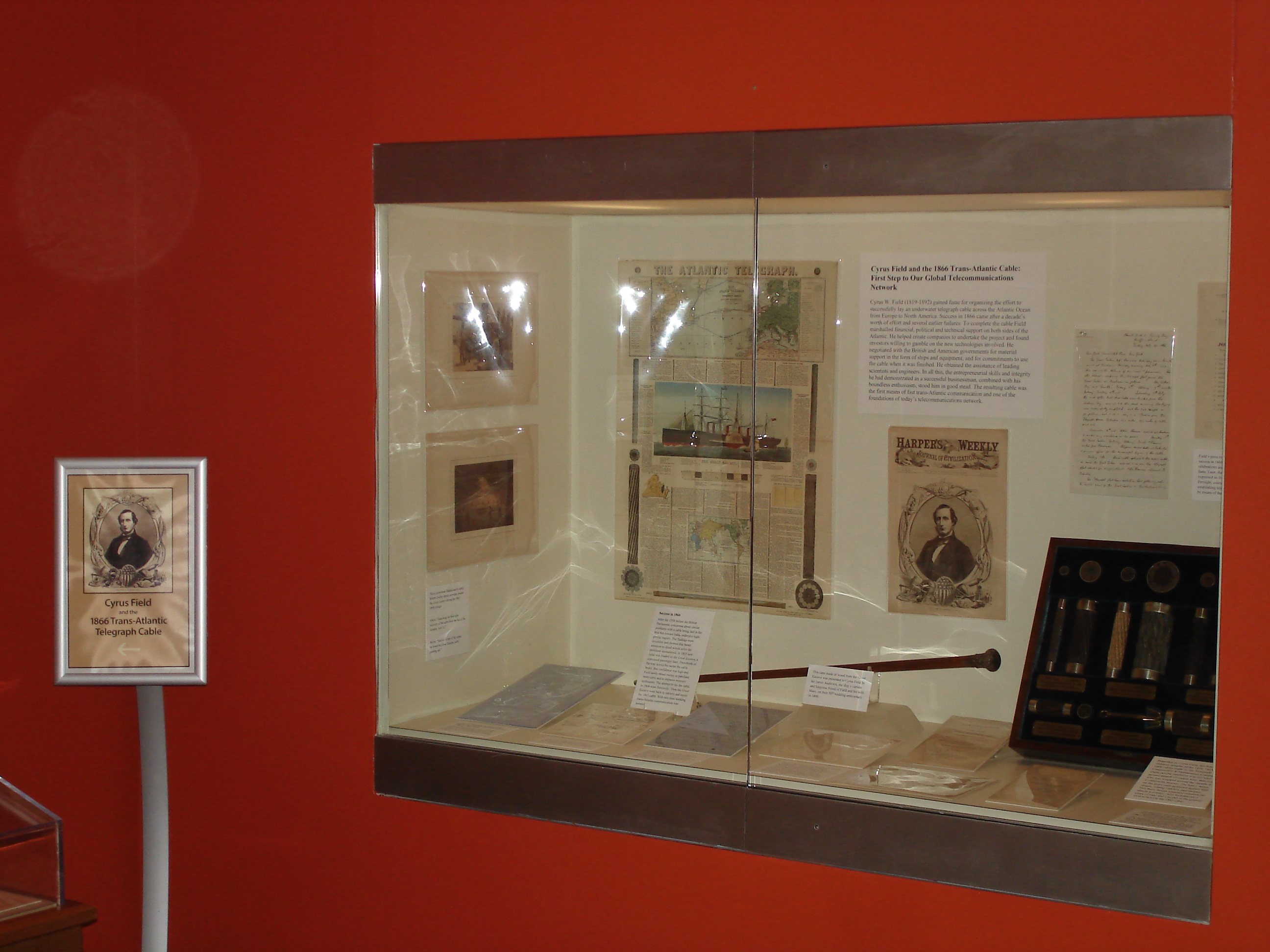 A view of the exhibit, looking into the corner. The wall is painted red and there is a display case set into the wall with a sign standing next to it giving the name of the exhibit. In the case are notes, letters, prints, a cane, pieces of cable, and notes/labels describing the objects
