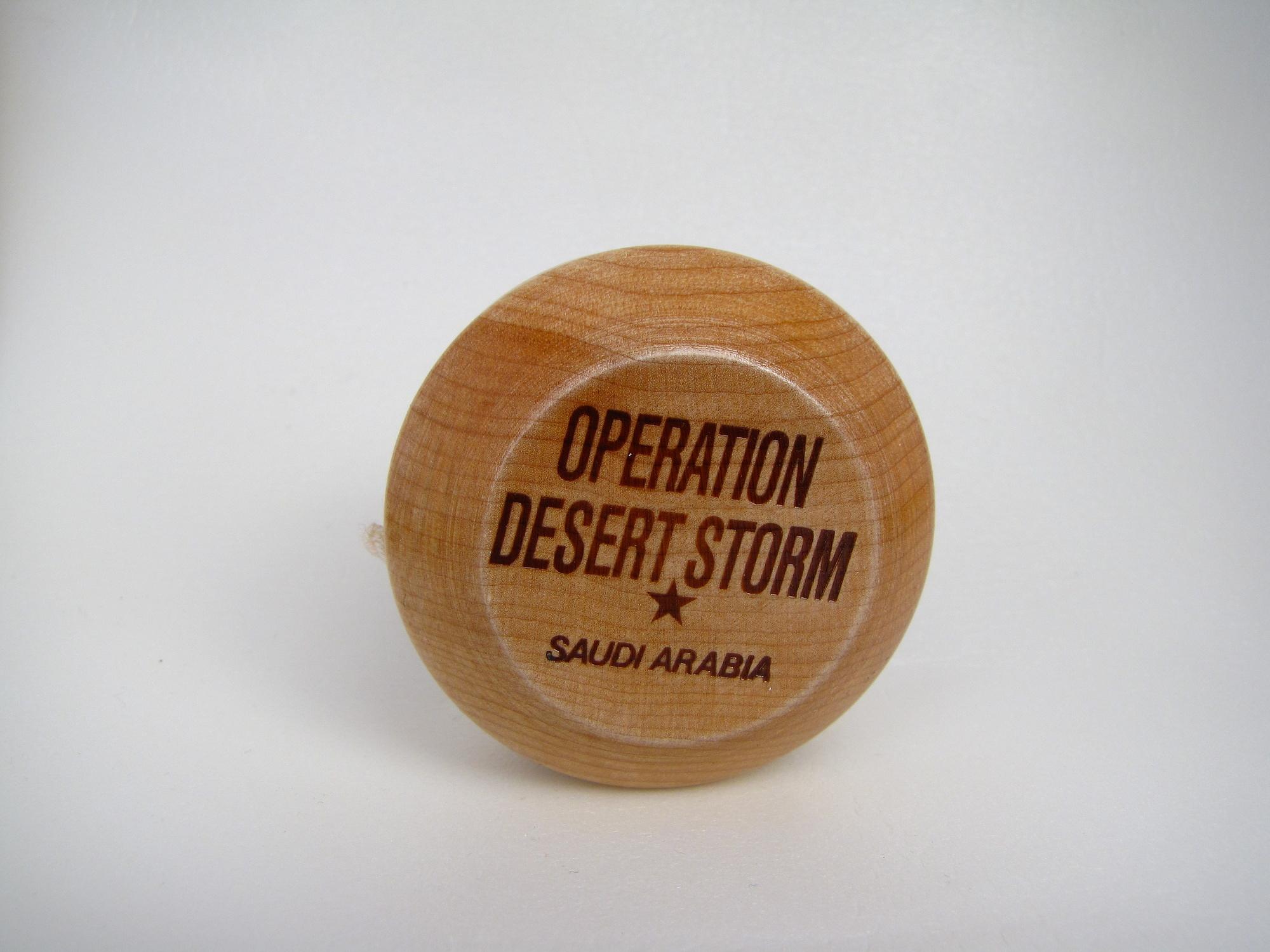 Wooden yo-yo with dark brown writing