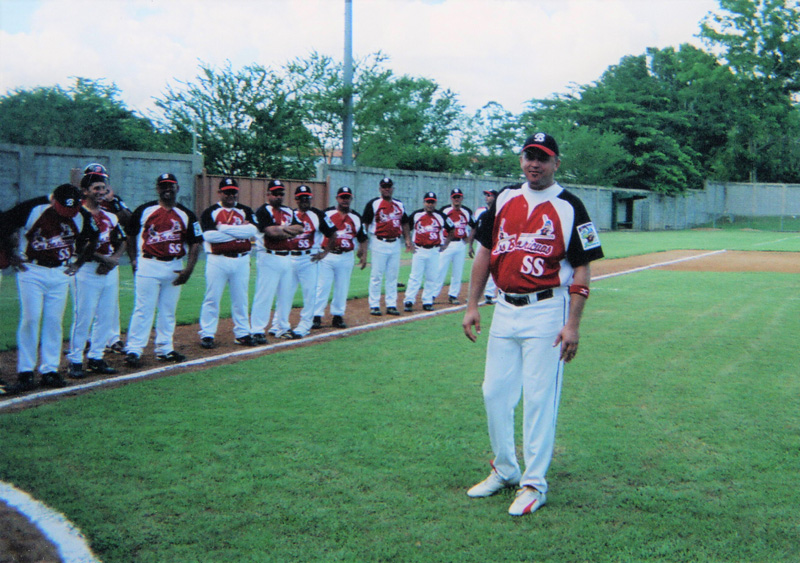 The Los Boricuas team line up on a baseball field, while team captain José Jusino stands in the foreground