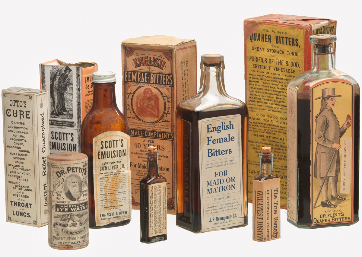 Photograph of a group of patent medicine bottles and boxes from the late 1800s and early 1800s. The bottles and boxes come in a wide range of sizes, with a large amount of text and a few iimages depicintg spoke-characters and stereotypes.